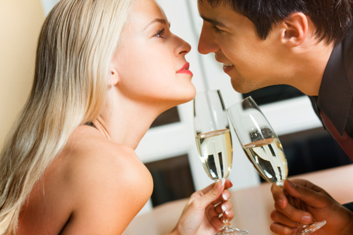 Couple kissing on romantic date or celebrating together at resta